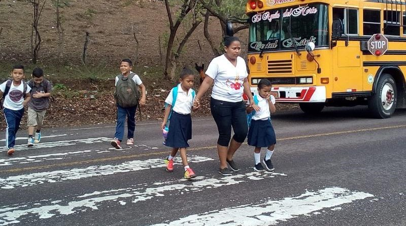 El lente del aficionado capta a la madre cruzando la calle con sus dos hijitas asidas de su mano.Protección de madre, bendita seas