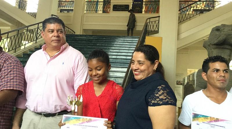 Ania Ponce  de San Miguelito recibe gozosa su certificado y otros premios por su obra en el I Certamen de Pintura Tradiciones de Mi Pueblo,Verano D´Amor, la acompaña la alcaldesa  Ana Clemencia Ávalos
