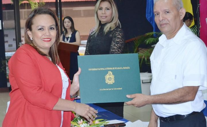Servidora pública recibe su título de parte de Sandi Peralta, director general de la Carrrera Administrativa Municipal (Cam)