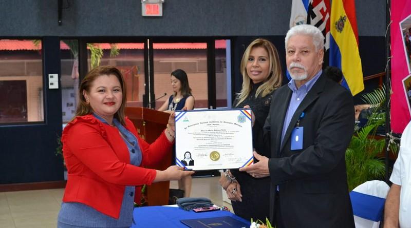 Hugo Gutiérrez, vicerrector de docencia, de  la UNAN-Managua, entrega título a servidora pública