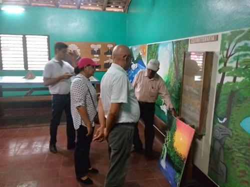 La presidenta de Inifom, Guiomar Irías y el director del Inc Luis Morales   observan pinturas de artistas nativos