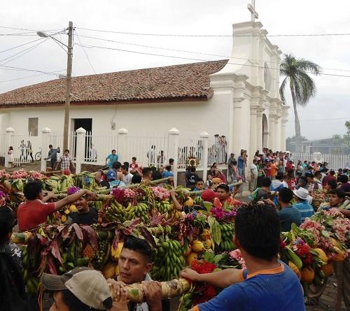 Desfile de varas con frutas y flores para la enramada