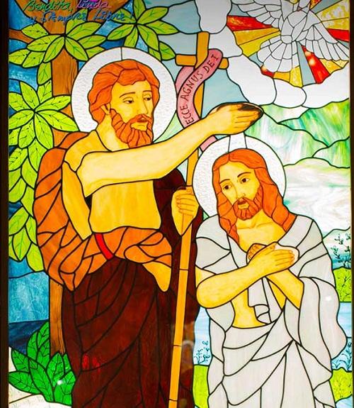 Uno de los vitrales de la iglesia muestra a San Juan Bautista bautiza a Jesús