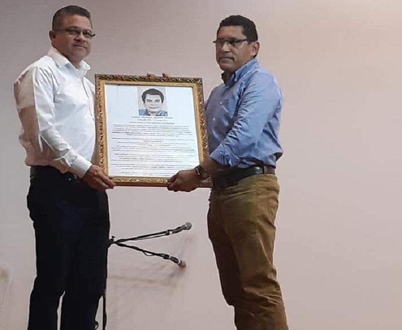 El alcalde de San Carlos Jony Gutiérrez y un familiar del profesor Carlos Aguirre, sostienen un retrato del especialista de la cultura e historia de Río san Juan