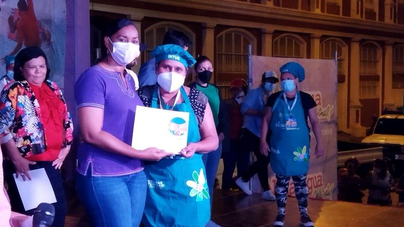 La co-directora de Intur, Anasha Campbell entrega certificado de participación a una protagonista